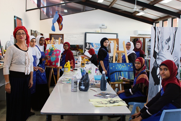 Art coordinator Amelia Joseph and Year 8 visual arts students with their works in progress.
