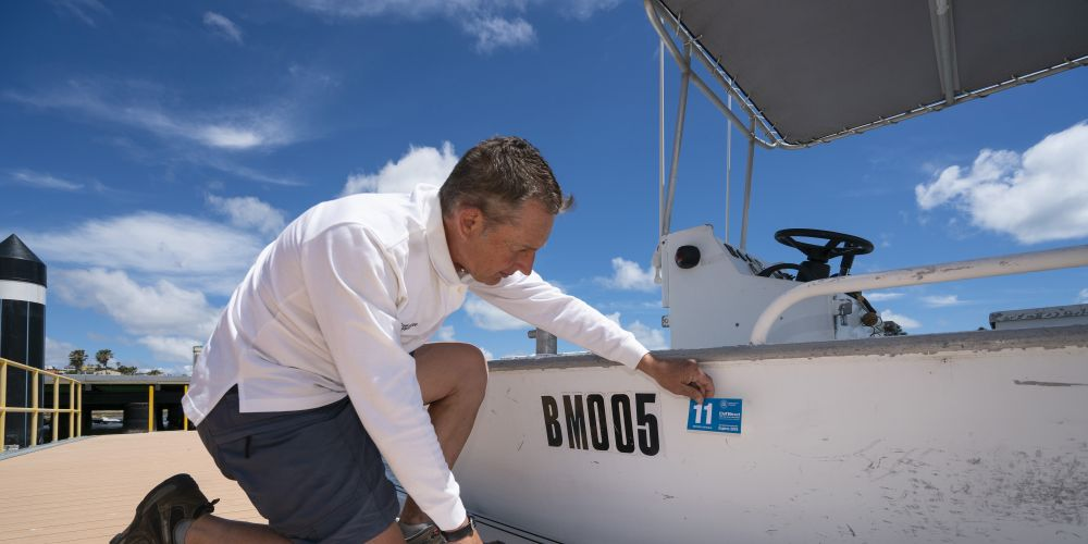 Marine education boatshed staff member Rod Marton showing how to correctly put a registration sticker on a boat.
