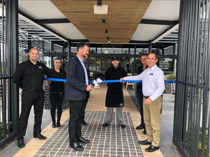 Wellard Residents Association president Matt Rowse cut the ribbon with proprietor Kevin Hughes, while staff and patrons looked on.