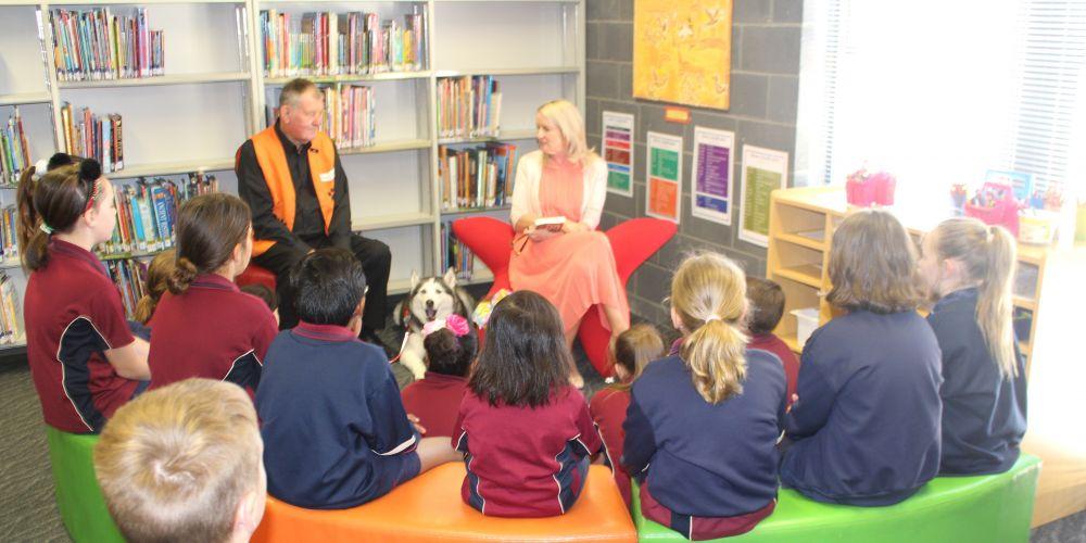 Harmony Primary School students enjoy a tale from Story Dogs volunteer Bob Kellar, his dog Mo and Never Stop Reading! ambassador Sarah McGowan.