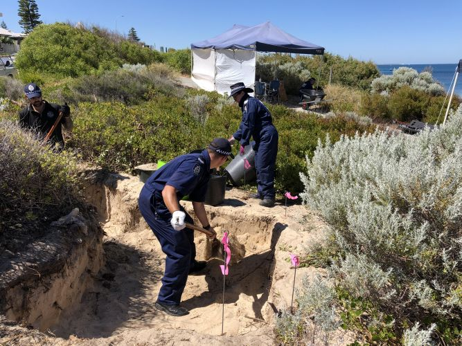 Police searching the dunes in Cottesloe this morning. Photo: Andrew Ritchie
