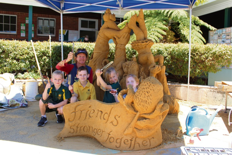 Fremantle sand sculptor Tim Darby with Connor Smith (7), Harry Archibald (8), Zara Kapica (7) and Grace Watters (7) in front of sculpture Friends Stronger Together.
