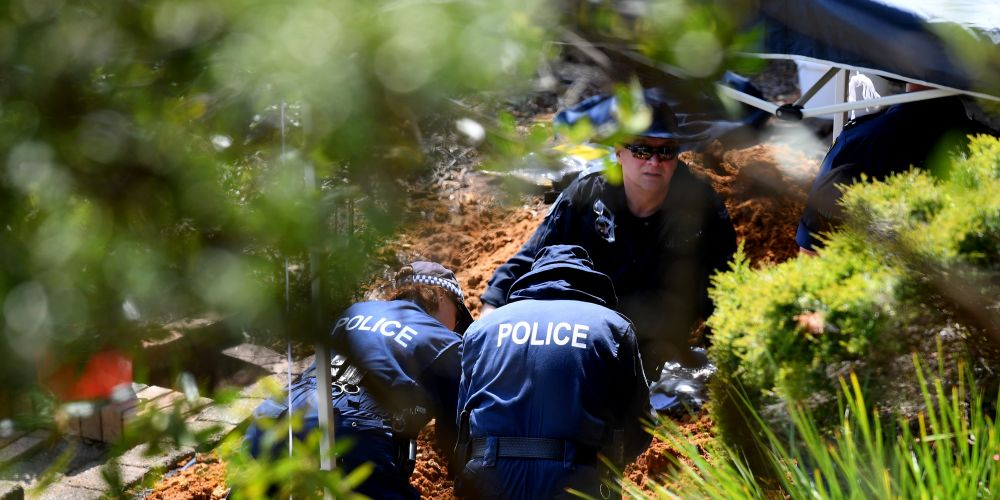 NSW Police and Forensic Services personnel are seen sifting through dirt as they search the former home of missing woman Lynette Dawson. Photo: AAP