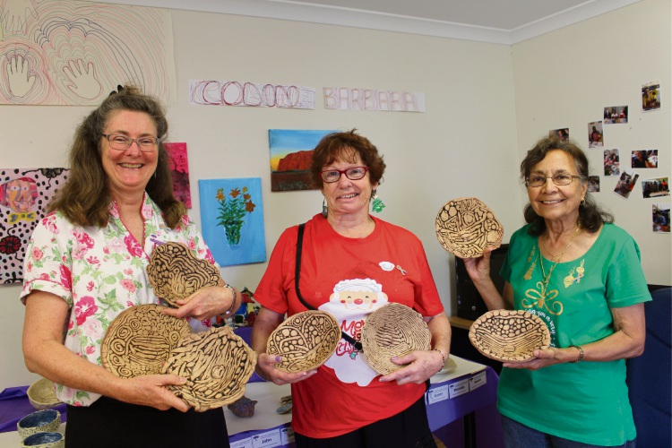 Artist in residence Sheryl Grant displaying 'squiggle pots' with art class participants Jacqui Carrington and Barbara Williams.