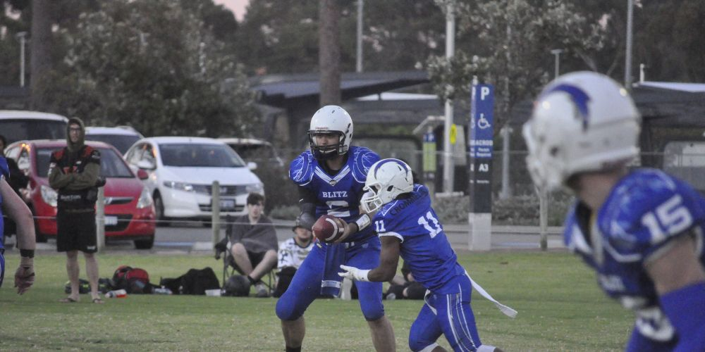 Blitz running back Andre Folkes prepares to take the ball from quarterback Andrew Perez.