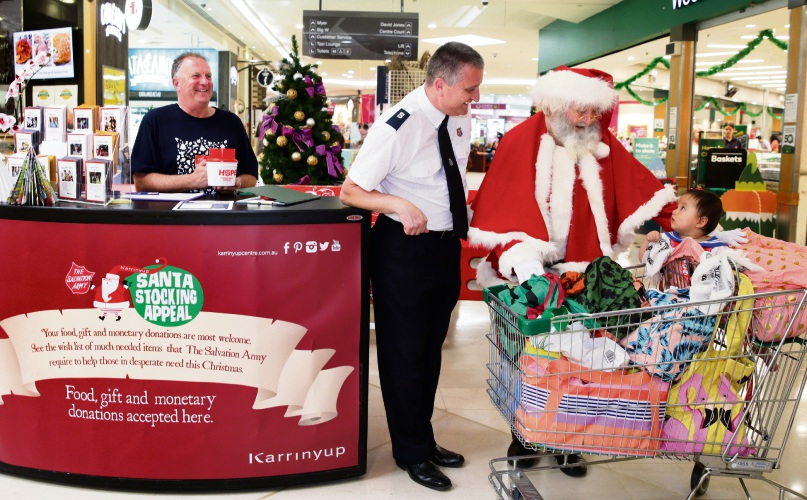 Nigel Pitkin and Warren Palmer from Salvation Army with Santa and Blake White. Picture: Martin Kennealey