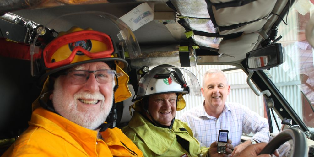 Gidgegannup volunteer firefighters Les Harris and Stuart MacKenzie check their mobile coverage with Telstra Regional General Manager Boyd Brown. Photo: Mark Thompson