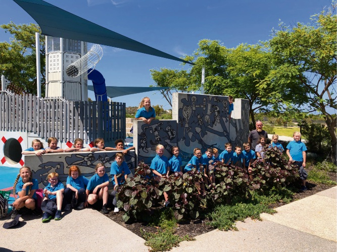 Mindarie Primary School students at the mural created by Scape-ism owner Jahne Rees.