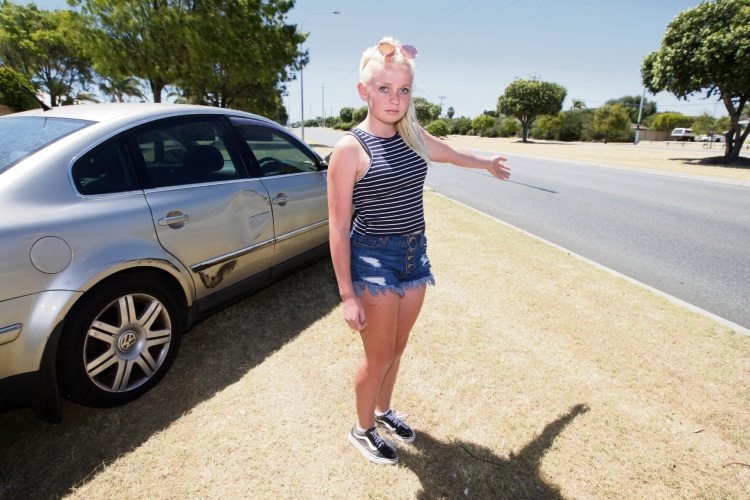 Emily with her mother Georgie Lloyd's damaged car. There are skid marks where the car was side-swiped.