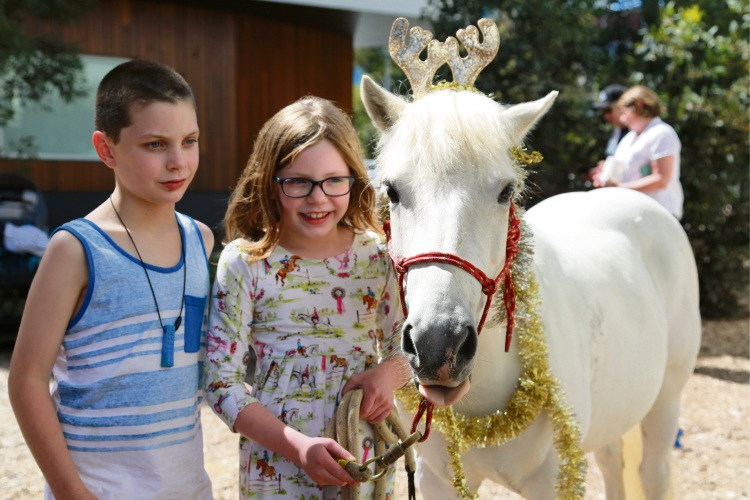 """Ronald McDonald House children Tess and Jake with a """"reindeer pony""""."""