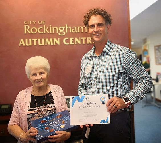 Autumn Centre member Audrey Hancock is presented with a certificate and a box of chocolates from coordinator Brett McDonald. Picture: City of Rockingham.