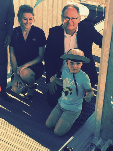 Mandurah MLA David Templeman switches on the seabin, helped by Elijah White and watched by City environmental education officer Tarnee Rutherford.