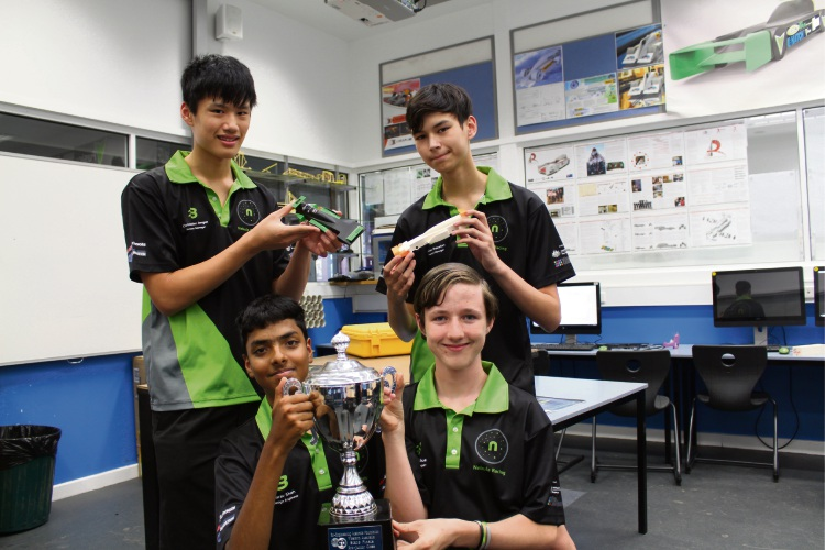 Aarav Shah (14) and Riley McGlue (14) with their State Champions trophy. BACK: Chris Jongue (15) and Caelan Shanahan (15) with a Nebula Racing model F1 car.