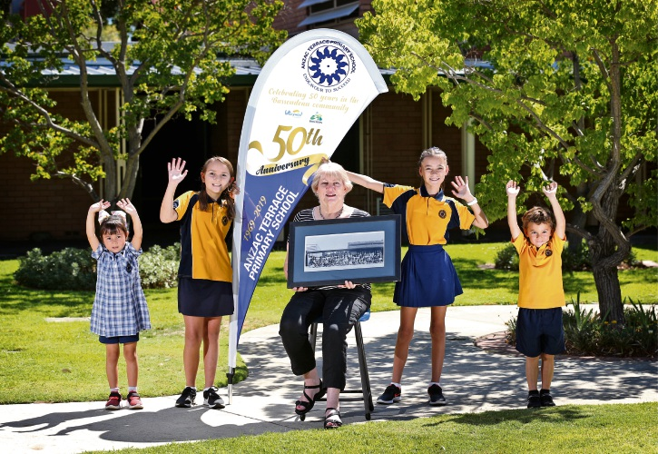 L-R: Jolina Lemke (5) from Pre-Primary, Phoenix Donoghue (11) from Year 6, Liz Page (Deputy Principal) holding a photo of the foundation students, Scarlett Smith (11) from Year 6 and Korey Ross (4) from Pre-Primary. Photo: David Baylis