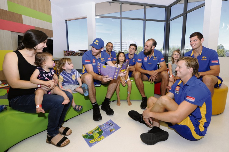 Eagle Jeremy McGovern reading to children in the Telethon Children's Ward play room. Picture: Chris Kershaw