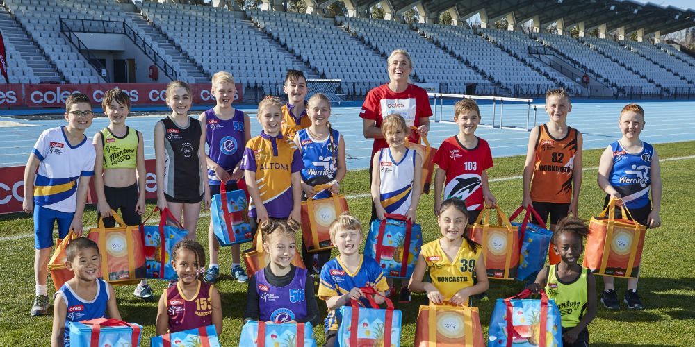 Sally Pearson and kids with Coles community bags which raise funds for Little Athletics.