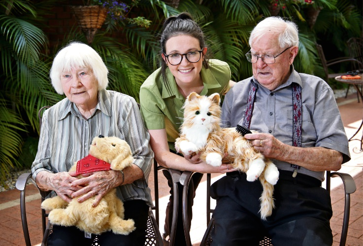 Concorde Aged Care Home residents Beryl Hartley (with Toby the dog) and Walter Hartley (with Marmalade the cat) are joined by senior occupational therapist Madelyne Glover. Picture: David Baylis