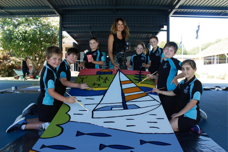 Emma Blyth with one of the panels from the mural she is painting with students from Mandurah Primary School.