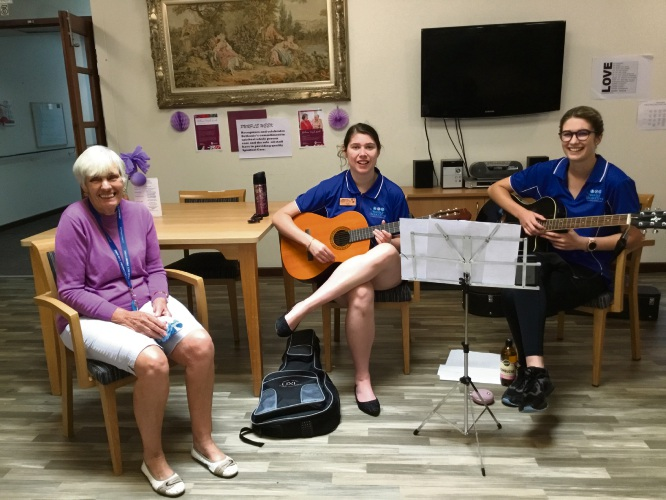 Proudly Productive Team Member Tayla Busher (middle) playing the guitar and singing with Proudly Productive work coach, Shelby Armstrong (right) and Bethanie Illawong resident  Karen Nicholson (left).