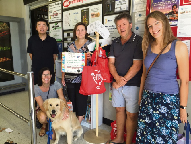 The owner of Seascapes IGA with association members Jo Sinker, Nick Benson, Gina Johnson, some boomerang bags, the socks donation box and (front) chairman Deb Maybury with Cooper.