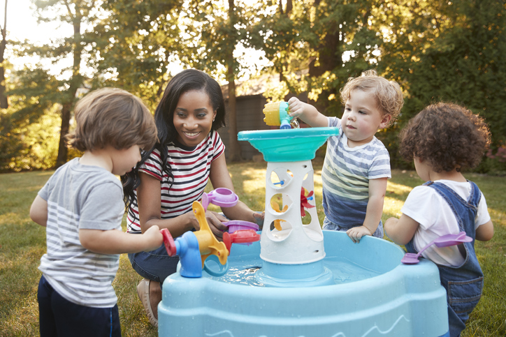 Mother And Young Children Playing With Water Table In Garden
