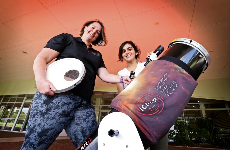 International Centre for Radio Astronomy Research cosmic communicator Cass Rowles and PhD candidate Pikky Atri with a 10-inch Dobsonian telescope. Picture: David Baylis. d491312.