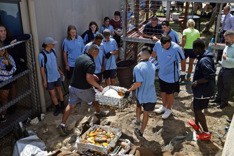 Mindarie Senior College teacher Joseph White and students open the hangi. Picture: Martin Kennealey d491778