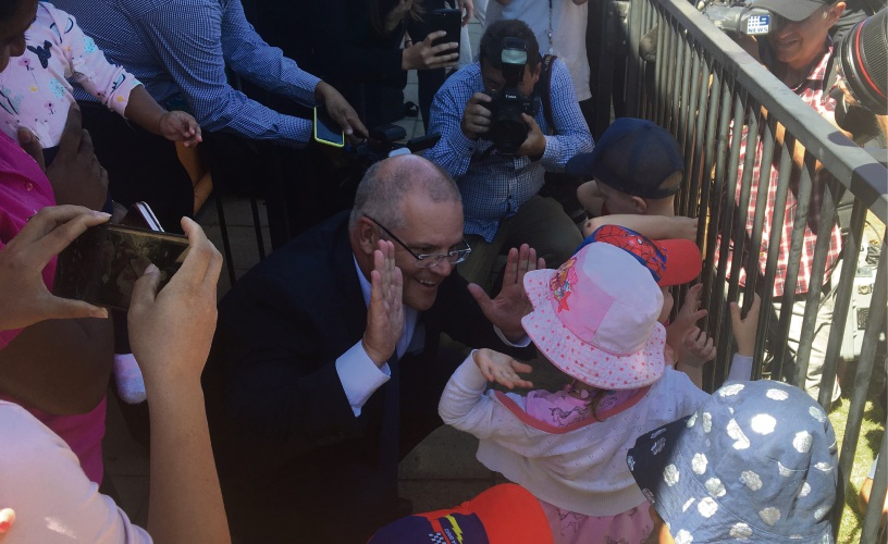 Prime Minister Scott Morrison scores a high-five during the quick visit to Carlisle.