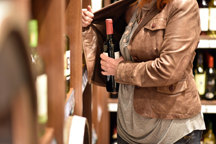 A woman steals a bottle of wine in a supermarket