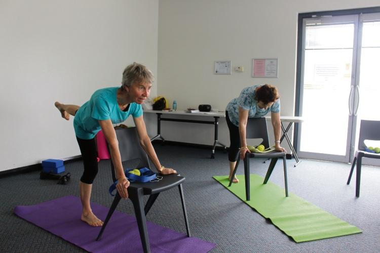 Yoga teacher Barbara Bowra and participant Kathy Deubert with a customised 'downward dog' pose for Parkinson's WA yoga class. Picture: Nadia Budihardjo