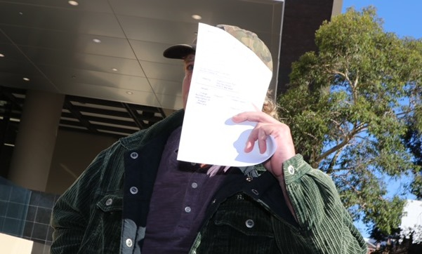 Forrestfield trick driver Carl Bridge covered his face from assembled media outside Perth Magistrates Court on Tuesday morning. Picture: Anton La Macchia