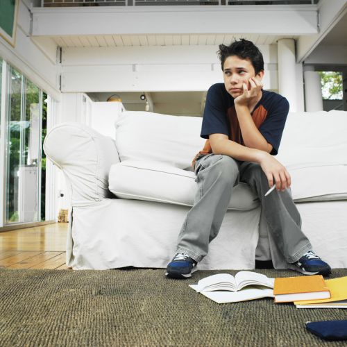 a young boy sitting on couch with notebooks scattered on floor