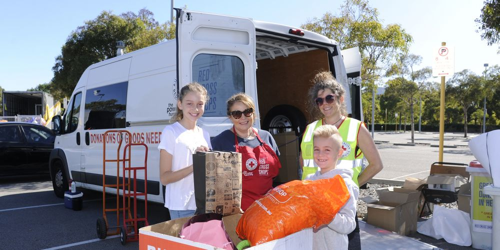 Stella Stroud (12) and Mitchell Stroud (8) with Red Cross staff members Charlotte Piot and Adrienne Martin