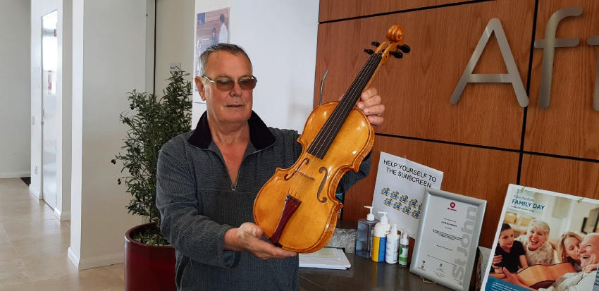 Kerren Horner with his first woodwork, a violin that took six months to complete.