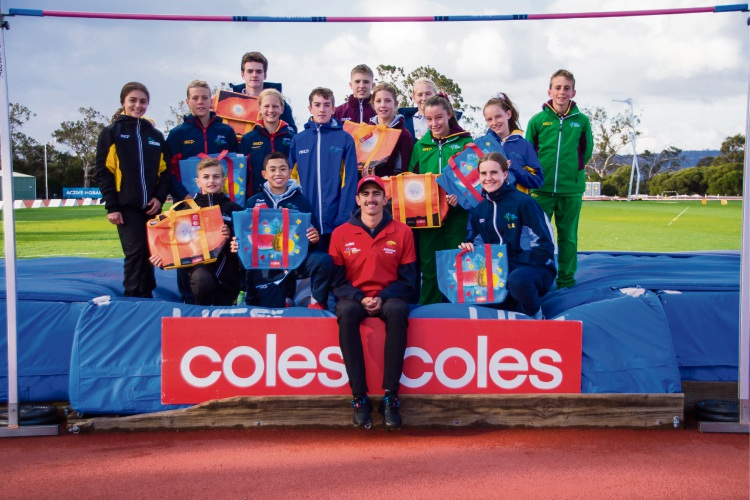 Olympian Brandon Starc with athletics juniors and the Coles community chiller bags.