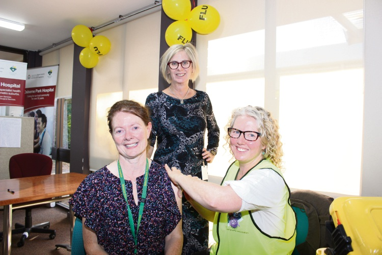 Osborne Park Hospital nurse co-director Marie Slater receives her flu vaccination from clinical nurse specialist Lisa Summers watched on by acting medical co-director Clare Matthews.