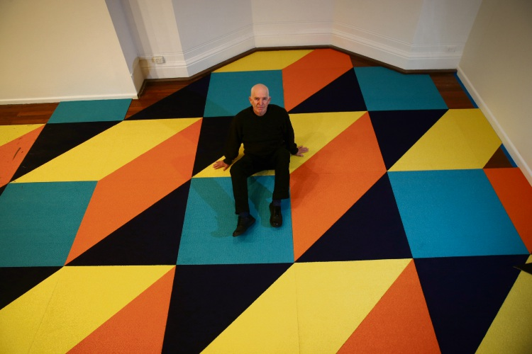 Artist Trevor Richards takes the weight off his feet atop his carpet art. Pic: Andrew Ritchie d493767b.