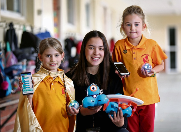 Manning Primary School Year 3 student Maddison Dunn (8), Curtin University volunteer Kira Molloy and Year 2 student Milla Meadows with their robots and devices for the Coding 4 Girls program. Picture: David Baylis