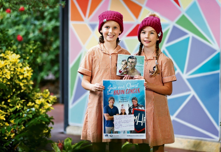 Willetton Primary School Year 5 students L-R: Leila Dawson (10) of Willetton and Jenna Bass (10) of Willetton. Jenna is holding a picture of her grandfather, who sadly passed away from brain cancer. His battle with the disease inspired the pair to fundraise Mark Hughes Beanies for Braincancer. Picture: David Baylis. d493896