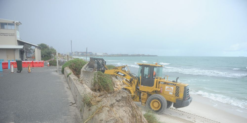 Fremantle Council excavator starts piling sand to protect heavily eroded Port Beach.  Pictures: Jon Bassett.