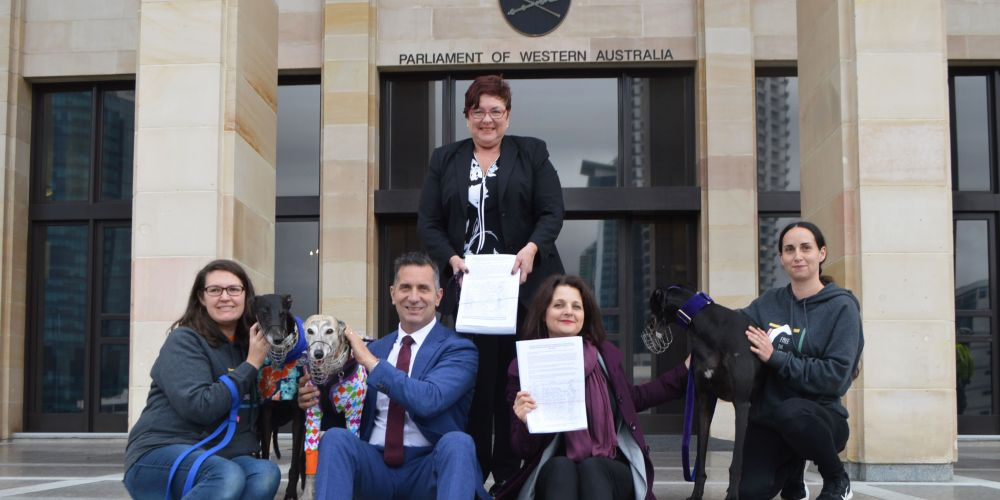 Free the Hounds treasurer Andrea Pollard, Racing and Gaming Minister Paul Papalia, North Metro MLC Alison Xamon, Free the Hounds president Alanna Christiansen, Maylands MLA Lisa Baker with muzzled greyhounds Max, Misty and Hope.