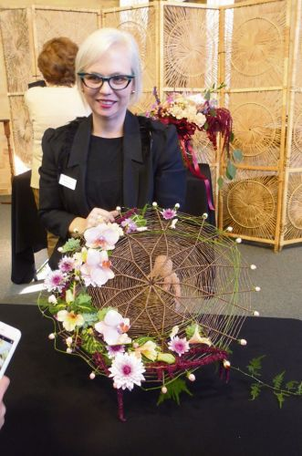 Mandurah Floral Art Group president Tanya Lee with a floral umbrella she designed.