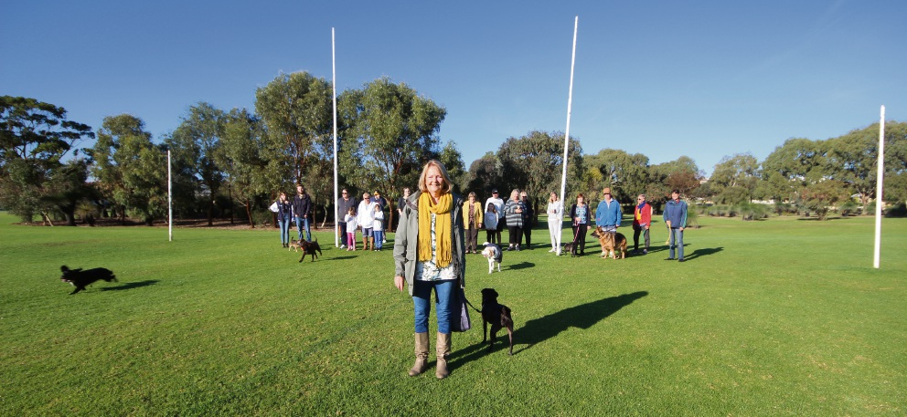 Merriwa resident Ros Casey with Biggles and other park users who want grass trees and bush retained at Addison Park.