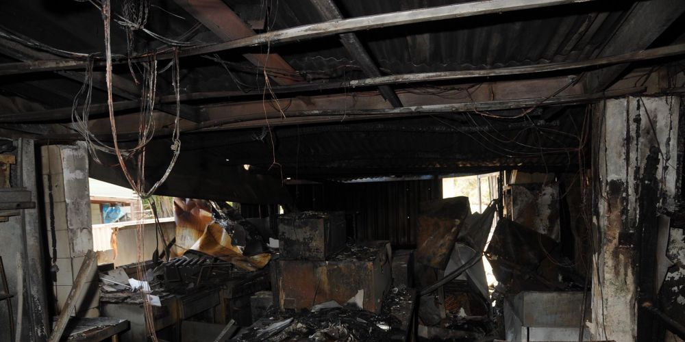 Two men have been charged with burning down a cafe in Perth's outer northern suburbs in an alleged insurance scam more than three years ago.