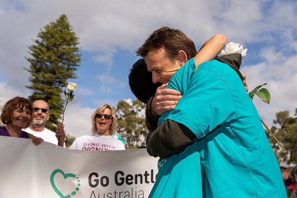 Belinda Teh is embraced by Adam Gilchrist at Kings Park before walking on to the WA Parliament with Euthanasia advocates in Perth. Picture: Will Russell/Getty Images