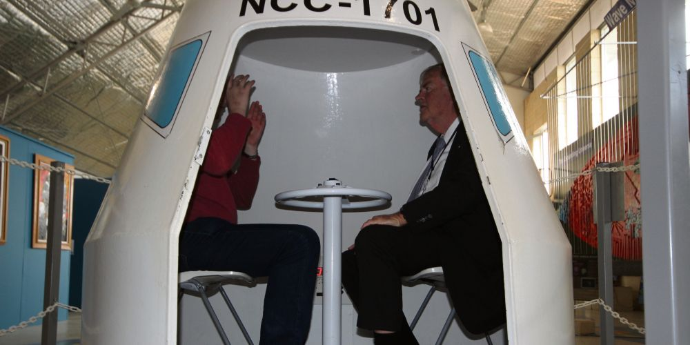 WA Governor Kim Beazley (right) goes for a spin in a space capsule at the Gravity Discovery Centre.