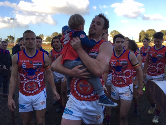 Michael Lourey walks off with his son and teammates after his 100th game for West Perth turned into a disappointing loss against premiers Subiaco. Picture: J Bianchini
