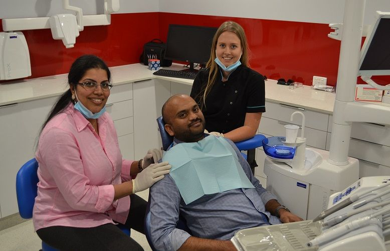 Principal dentist Dr Ajitha Kanupuru and assistant  Ashley McKay with patient Anand Kandavelu.