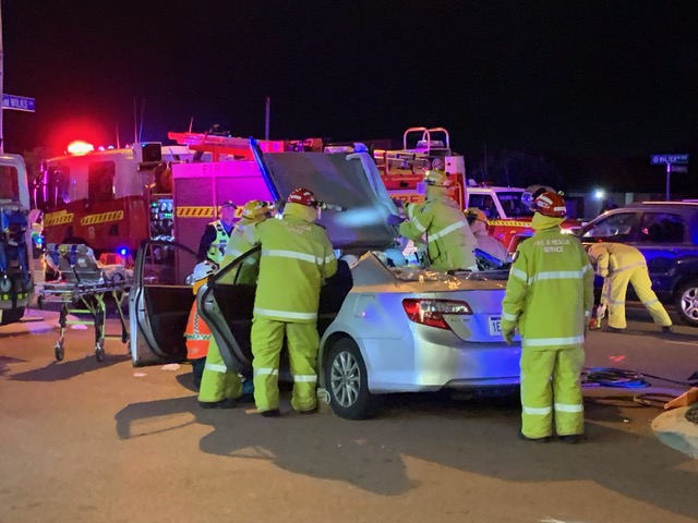 Emergency workers try to free occupants of the Toyota sedan. Picture: Anton La Macchia