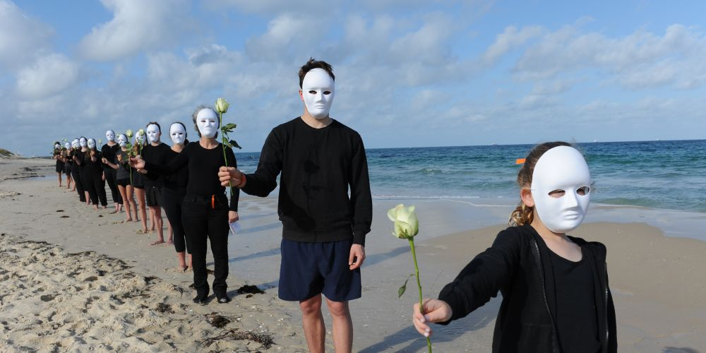 Unmasked saw black clad, masked figures carrying rose emerge from the water. Pictures: Jon Bassett.